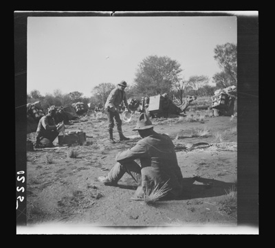 Bert Oliffe (left) and Frank Feast washing dishes while Donald Mackay (foreground) relaxes, central Australia, 1926. Photograph by Herbert Basedow